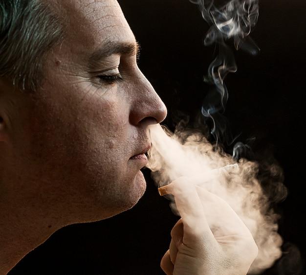 Man roken sigaret op zwarte achtergrond, knappe jonge man roken sigaret, mystery man met sigaar en rook geïsoleerd op zwarte achtergrond Gratis Foto