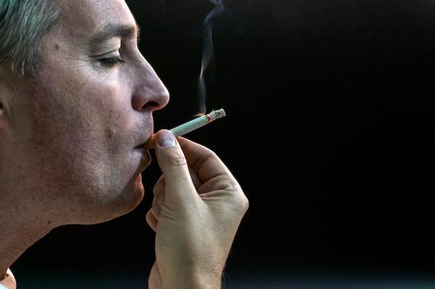 Man roken sigaret op zwarte achtergrond, knappe jonge man roken sigaret, mystery man met sigaar en rook geïsoleerd op zwarte achtergrond Premium Foto