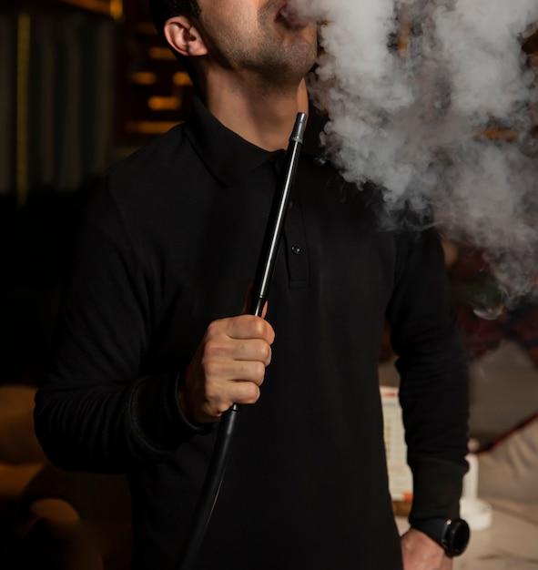 Man rookt shisha en trekt de rook in Gratis Foto