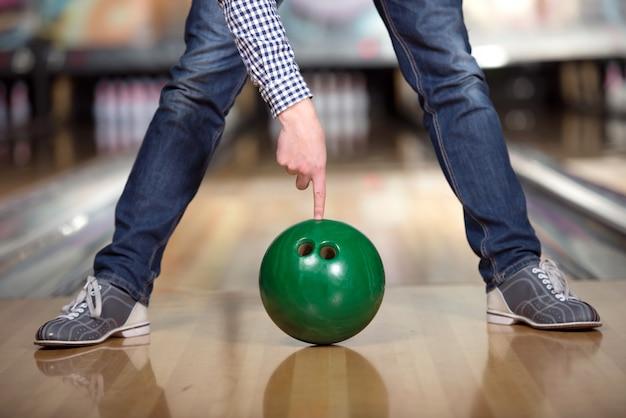 Man's benen en groene bowlingbal. Premium Foto
