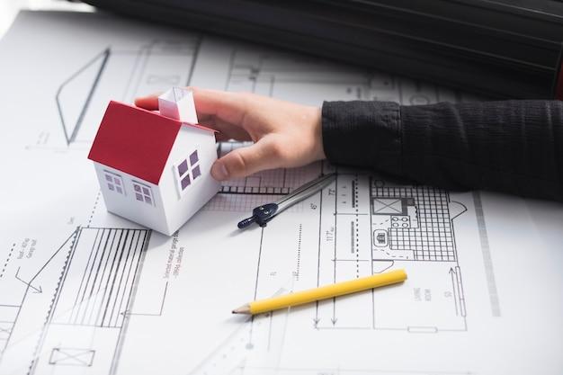 Man's hand met huis-model op blauwdruk op kantoor Gratis Foto