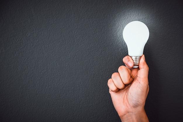 Man's hand met led-gloeilamp over zwarte muur Premium Foto
