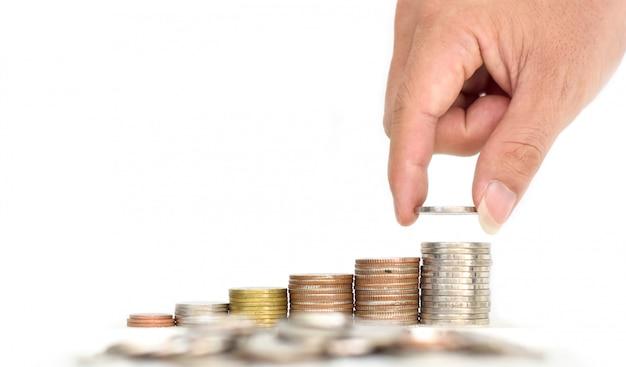 Man's hand zet geldmunten op stapel munten Premium Foto
