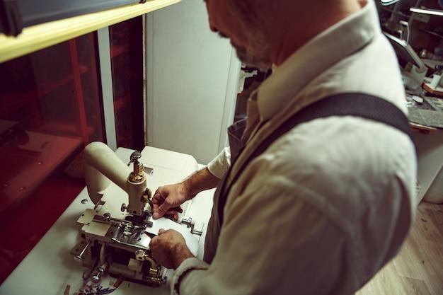 Man's handen achter het naaien. leerwerkplaats. textiel vintage industrieel. de man in vrouwelijk beroep. gendergelijkheid concept Gratis Foto
