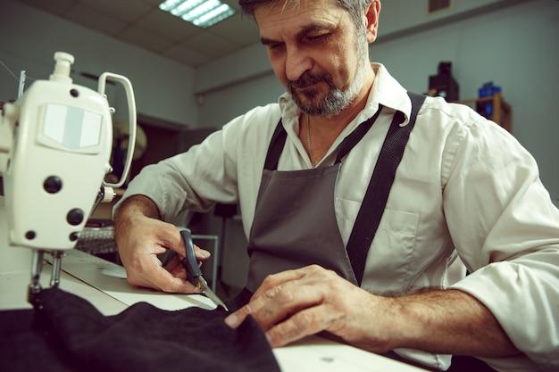 Man's handen en naaimachine. leerwerkplaats. textiel vintage industrieel. de man in vrouwelijk beroep. gendergelijkheid concept Gratis Foto
