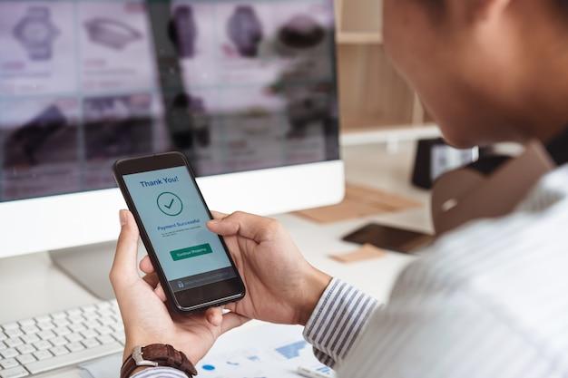 Man's handen met smartphone en succesvolle online betaling. mobiel portemonnee betalingsconcept. Premium Foto