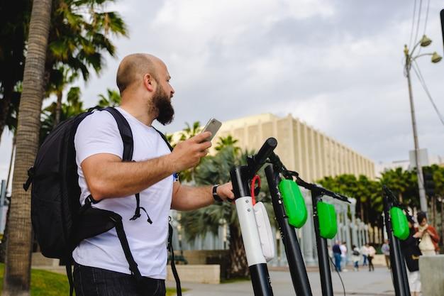 Man scannen qr-code met zijn telefoon voor elektrische scooter huren Premium Foto