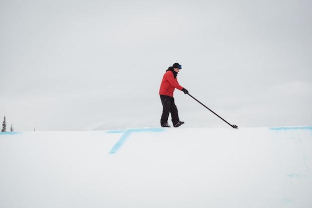 Man schoonmaak sneeuw in skigebied Gratis Foto