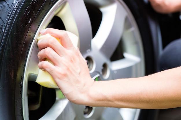 Man schoonmaken wielrand terwijl car wash Premium Foto