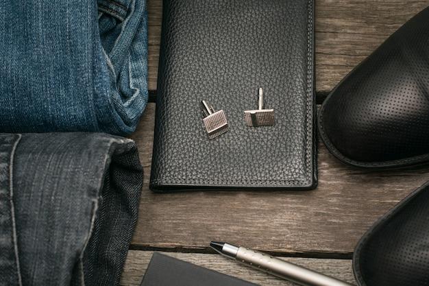 Man set voor de dag van portemonnee, jeans en manchetknopen op een houten bord. Premium Foto