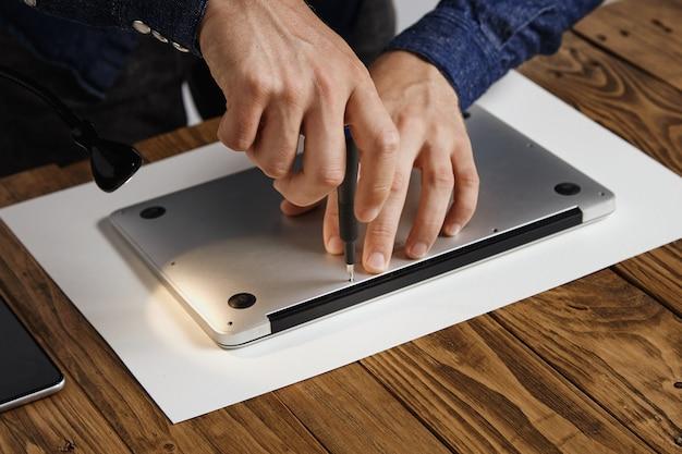 Man sluit topkoffer van metalen dunne laptop om hem weer in elkaar te zetten na het repareren, schoonmaken en repareren in zijn laboratorium Gratis Foto