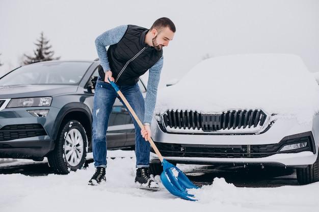 Man sneeuw verwijderen met schop door de auto Gratis Foto
