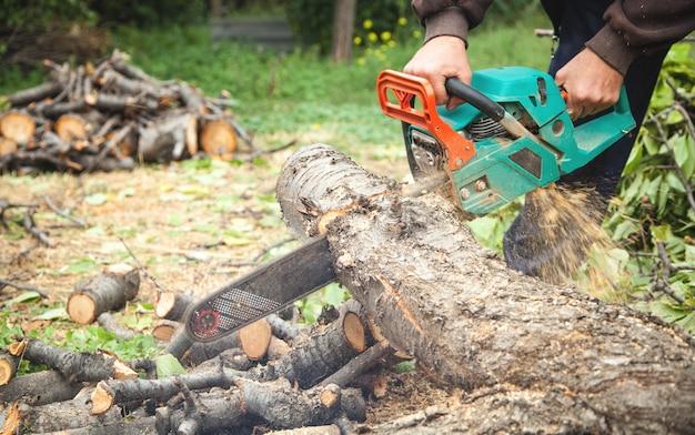 Man snijden hout met een kettingzaag. Premium Foto