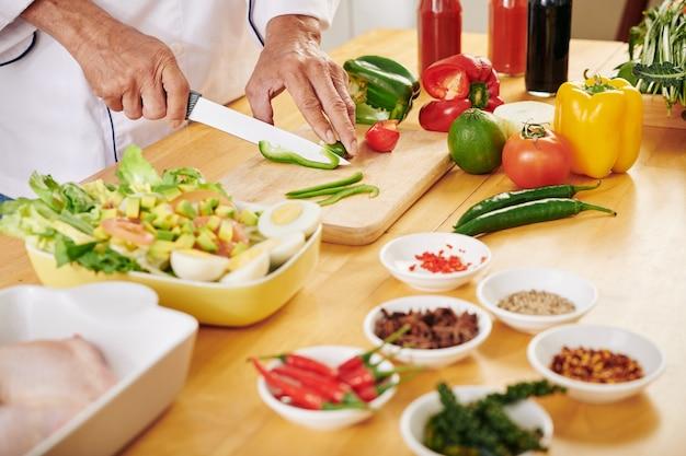 Man snijden van verse groenten Premium Foto