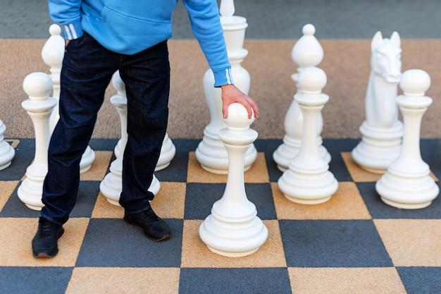 Man speelt gigantisch schaken buitenshuis Premium Foto