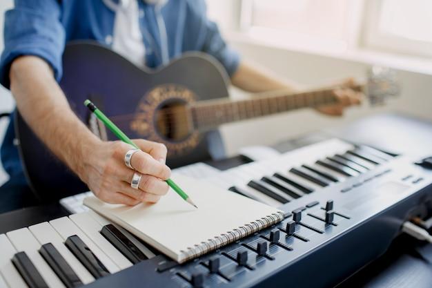 Man speelt gitaar en produceert elektronische soundtrack Premium Foto