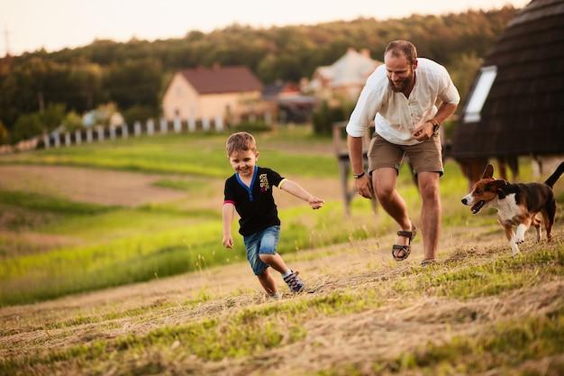 Man speelt met zijn zoon en een hond op het veld Gratis Foto