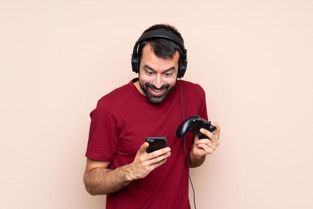 Man spelen met een video game controller over geïsoleerde muur verrast en het verzenden van een bericht Premium Foto