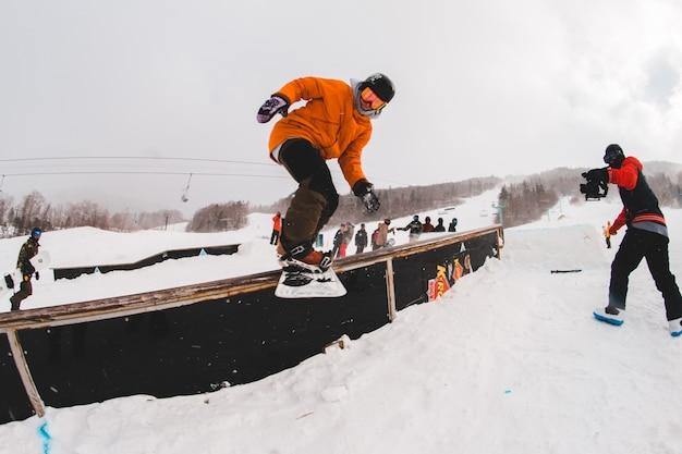 Man spelen met snowboard in de winter Gratis Foto