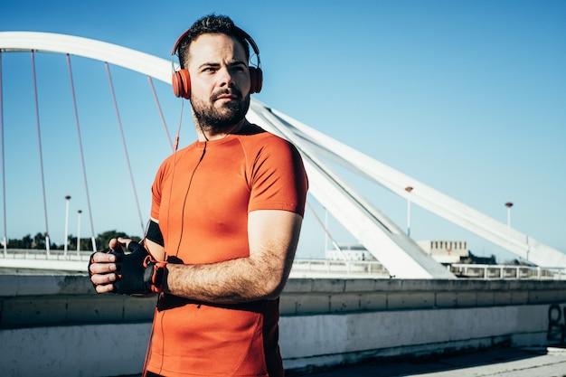 Man sporten en luisteren naar muziek met een koptelefoon Premium Foto