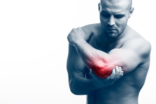 .man sportlichaam houdt een zieke elleboog vast Premium Foto