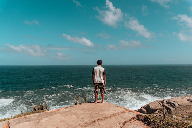Man staande op de rotsen omgeven door groen en de zee onder zonlicht en een blauwe lucht Gratis Foto