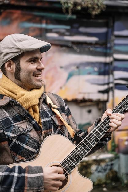 Man staat op straat en speelt akoestische gitaar. Premium Foto