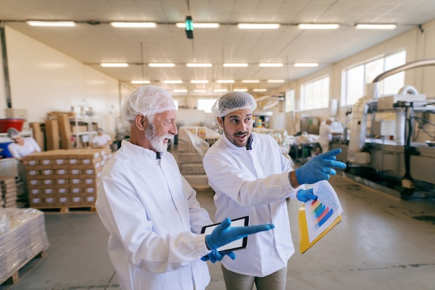 Man stapelen dozen terwijl andere man staan en tablet gebruiken. voedsel fabriek interieur. Premium Foto