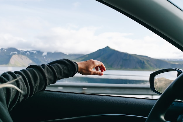 Man steekt zijn hand uit tijdens het autorijden Gratis Foto