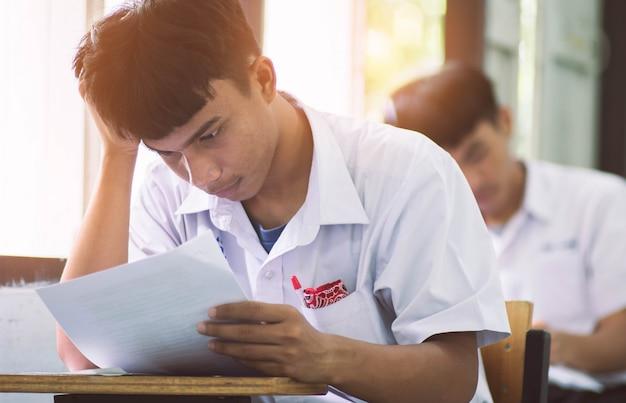 Man student lezen en schrijven van examen met stress. Premium Foto