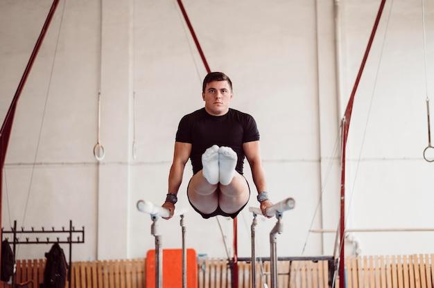 Man training op parallelle staven Premium Foto