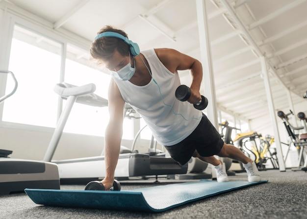 Man uit te werken op de mat in de sportschool Gratis Foto