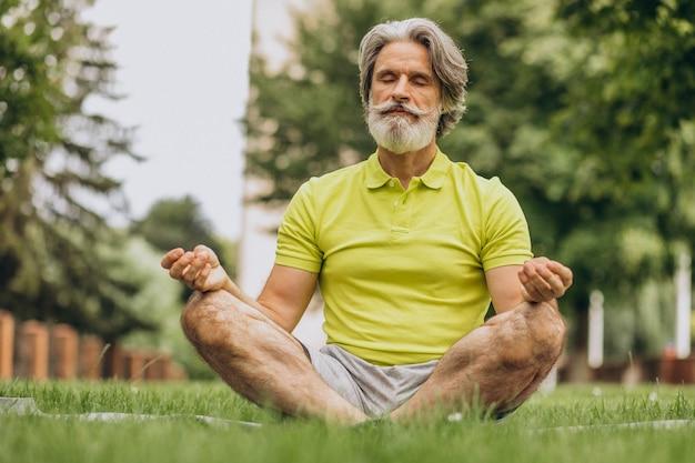 Man van middelbare leeftijd beoefenen van yoga op mat in park Gratis Foto
