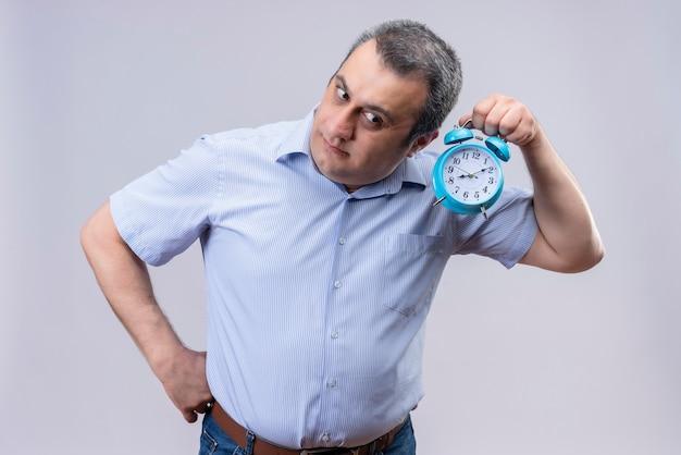 Man van middelbare leeftijd dragen blauw verticaal gestreept overhemd luisteren naar klok tikkende geluid blauwe wekker houden op een witte achtergrond Gratis Foto