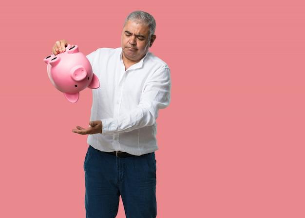 Man van middelbare leeftijd, verdrietig en teleurgesteld, met een biggenbank, geen geld over, probeert iets uit te halen, gezicht van woede en angst, concept van armoede Premium Foto
