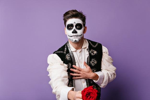 Man verliefd op gezichtskunst geeft prachtige roos, poseren voor portret in lila muur. Gratis Foto
