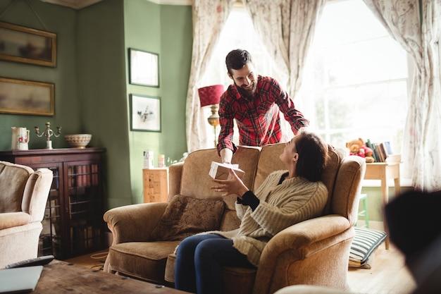 Man verrassende vrouw met een geschenk in de woonkamer Gratis Foto