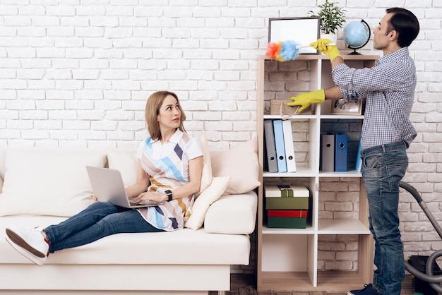 Man verwijdert stof van plank en vrouw in appartement Premium Foto