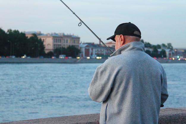 Man vissen op de promenade van de stad Premium Foto