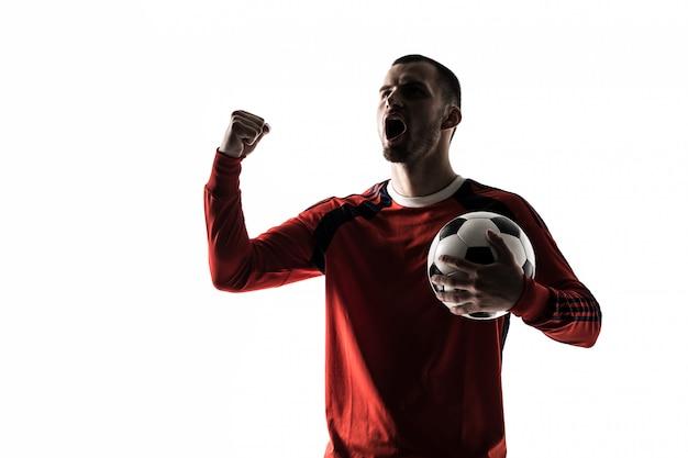 Man voetbal voetballer silhouet in studio geïsoleerd op wit staat met een bal overwinning Gratis Foto