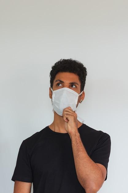Man volwassen zwarte dragen coronavirus masker denken geïsoleerd op wit Premium Foto