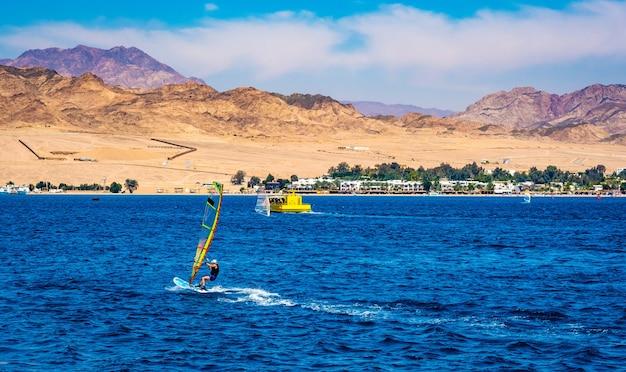 Man vrije tijd doorbrengen met extreme windsurfsport in blauwe zee Premium Foto