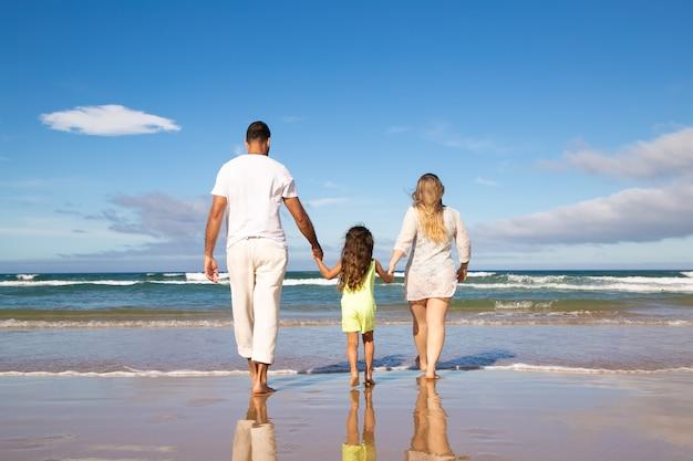 Man, vrouw en kind in bleke zomerkleding, wandelen op nat zand naar zee, vrije tijd doorbrengen op het strand Gratis Foto