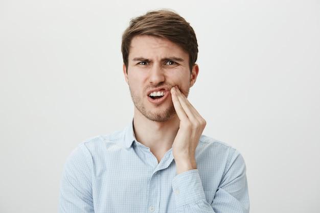 Man wang aanraken en grimassen van pijn door kiespijn, tandarts nodig Gratis Foto
