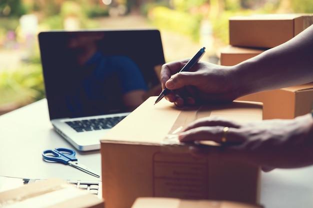 Man werknemer schrijven klant adres leveren verzending online verkoop. kleine ondernemer. verzending online verkoop Premium Foto