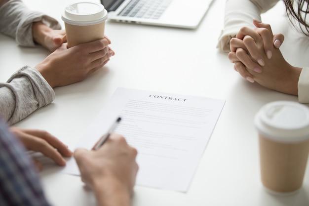 Man zet handtekening op contract, klanten ondertekenen document concept, close-up Gratis Foto
