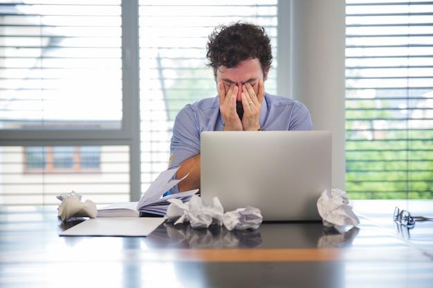 Man ziet er moe uit tijdens het werken Premium Foto