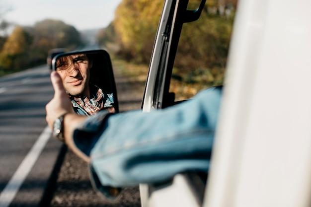 Man zijn spiegel in de auto aanpassen Gratis Foto