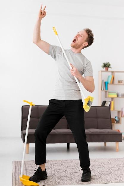 Man zingen op bezem tijdens het schoonmaken Gratis Foto