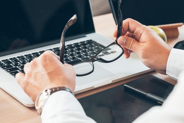 Man zit aan bureau thuis en houdt zijn bril vast, Premium Foto